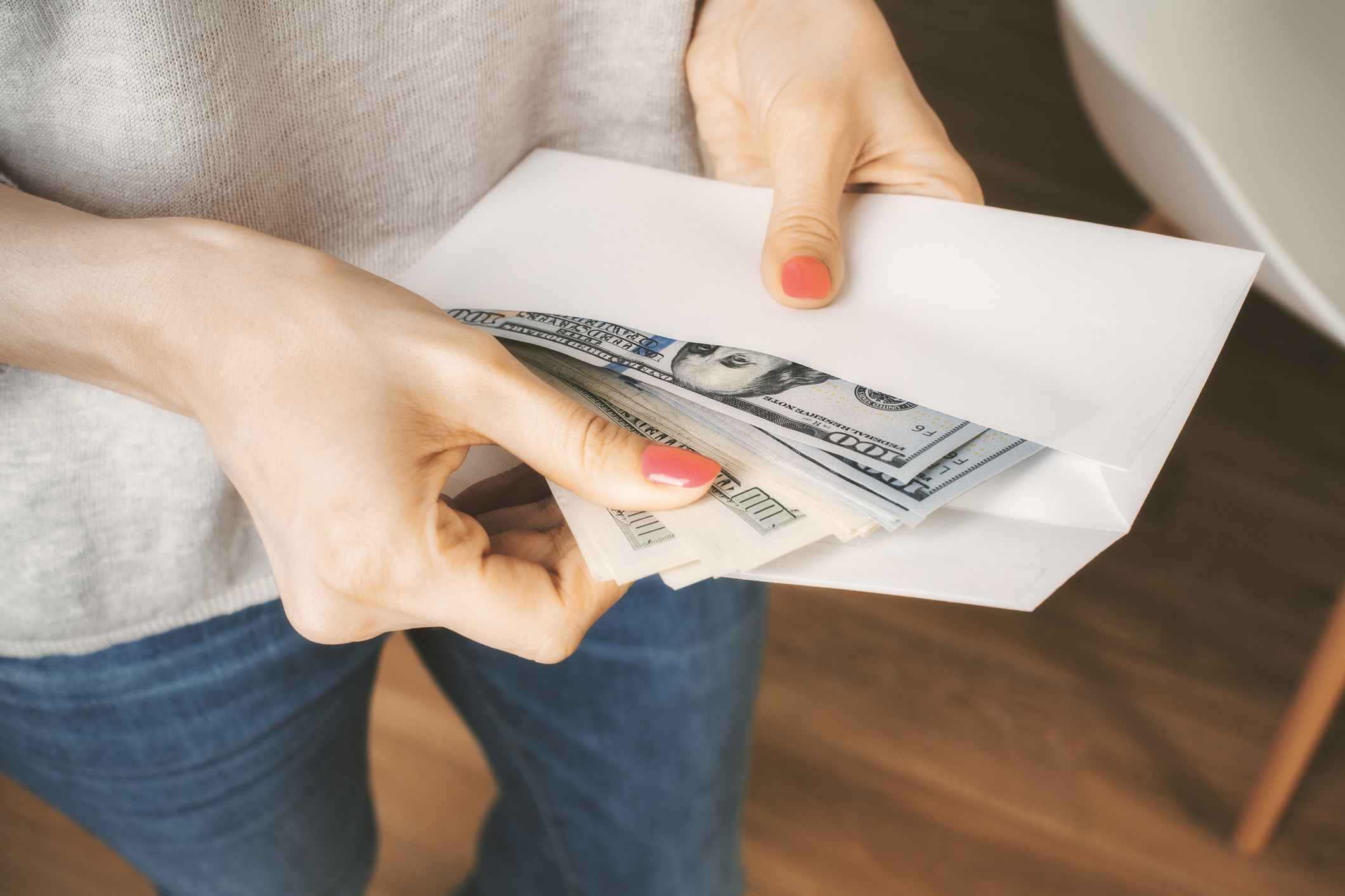 Person holding envelope with cash