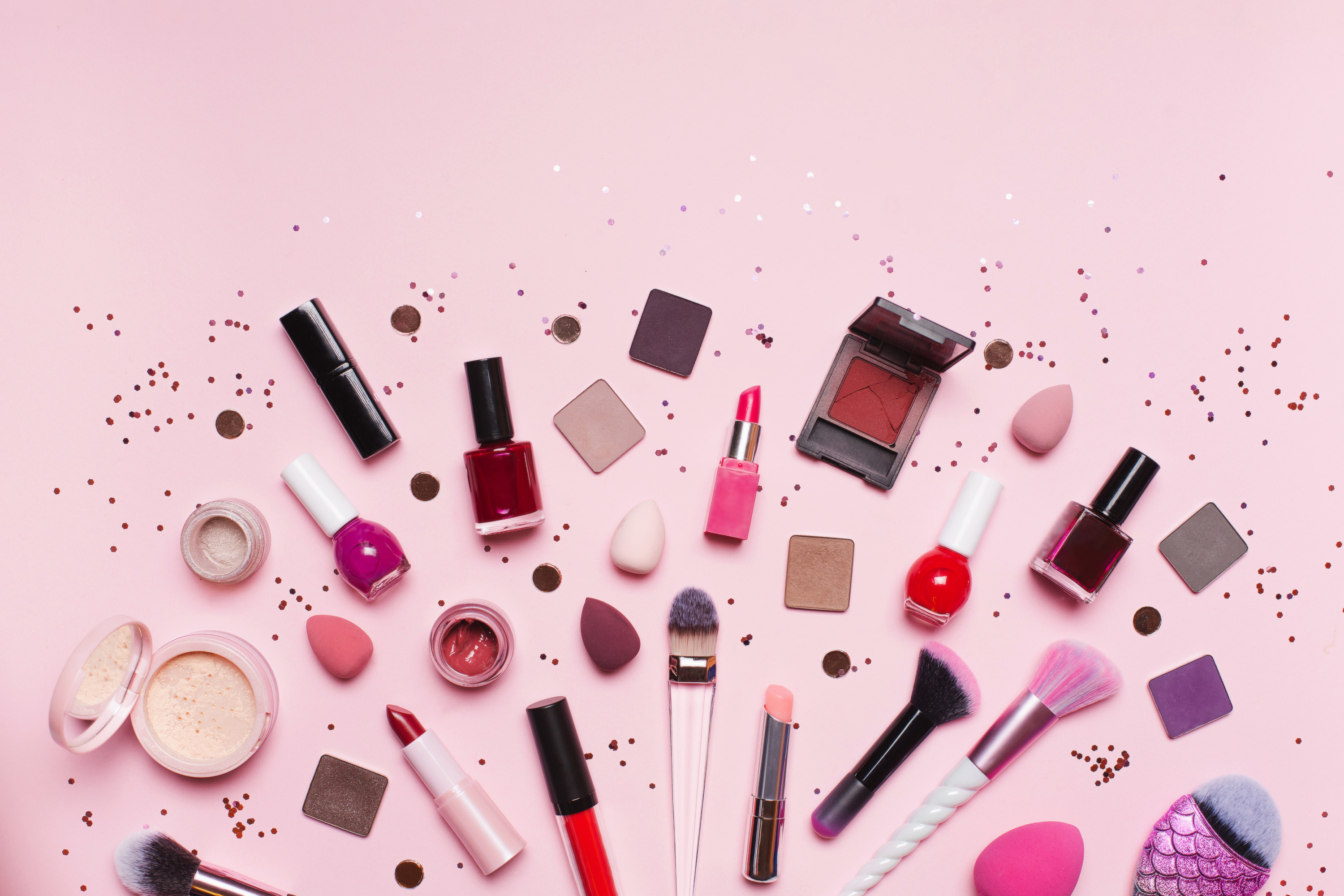 set of assorted tools and products for makeup application placed near shiny glitter on pink background