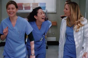 Meredith Grey smiles as she swings her arms back and forth, Cristina Yang is bent over laughing, and Lexie Grey has her head turned towards both of them with a frustrated expression.