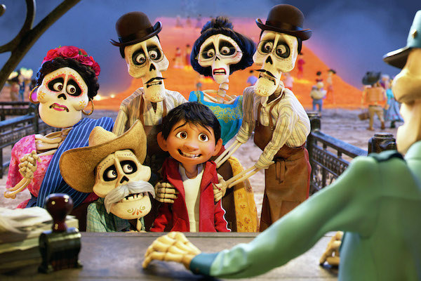 Miguel (voiced by Anthony Gonzalez) smiling nervously with his deceased family members.