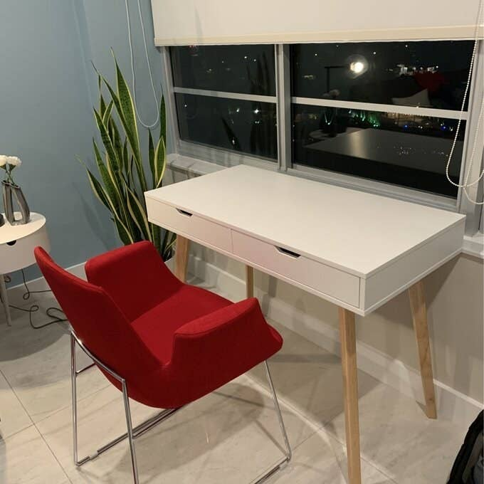 The white desk with natural wood legs in a reviewer's room