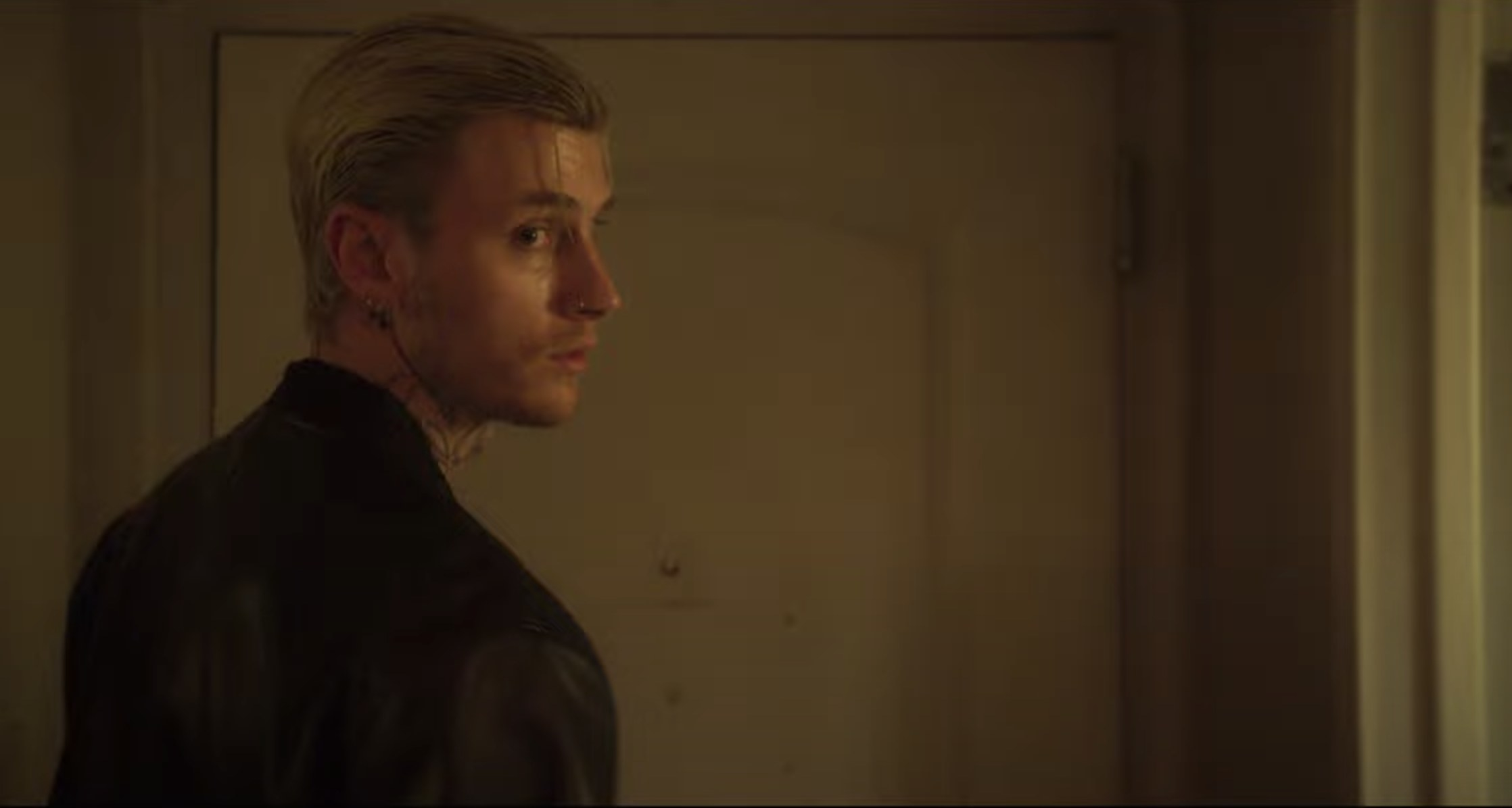MGK looks back while heading out of a door in a screenshot from the film