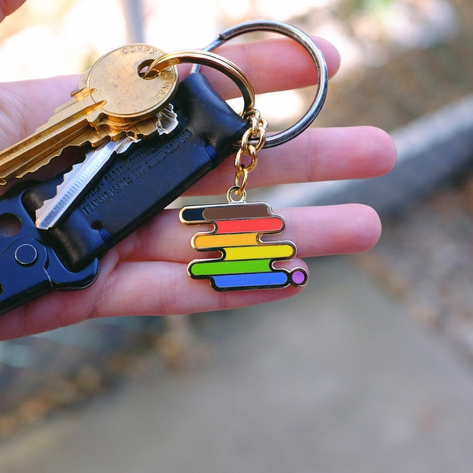QPOC Pride keychain with rainbow design on a set of keys
