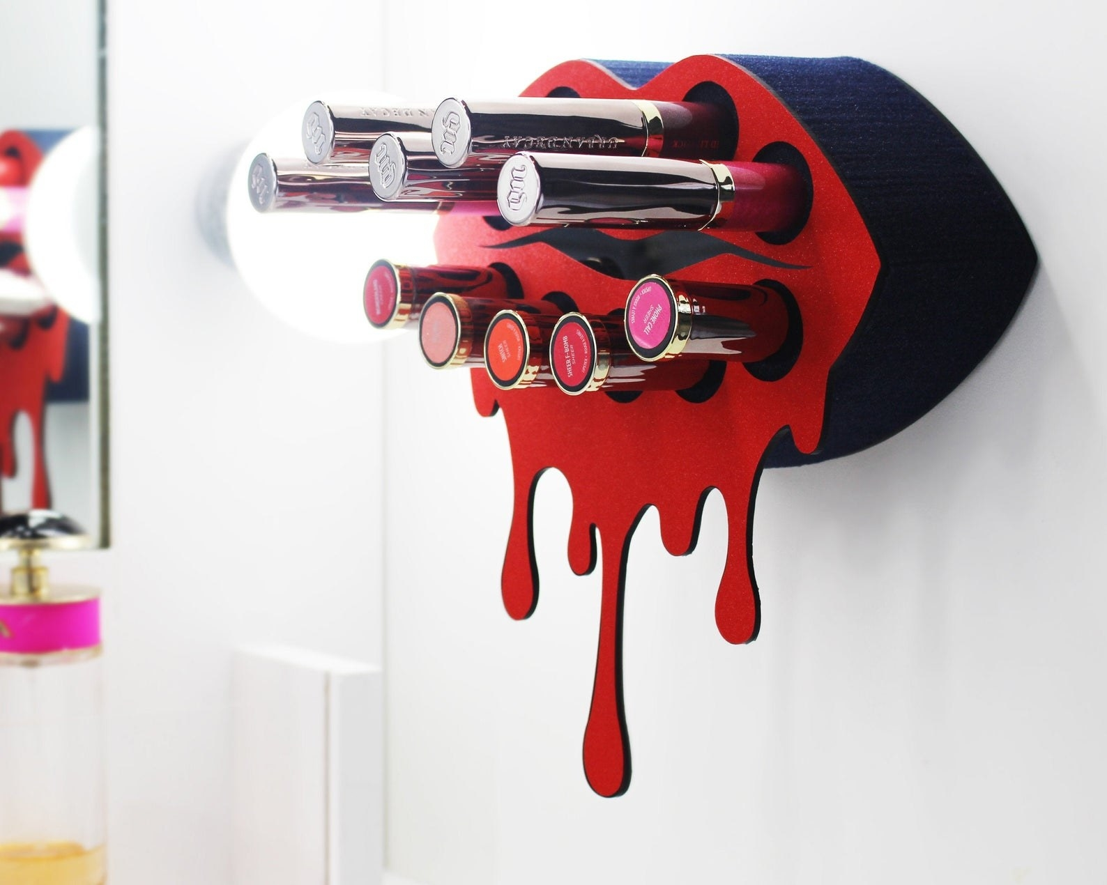 the lip-shaped lipstick holder holding a variety of lipsticks and glosses
