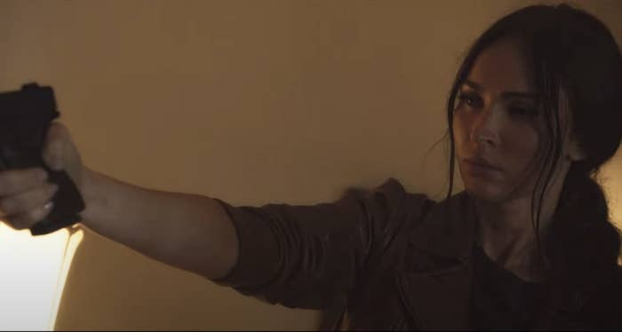 Megan holds up a gun in the film