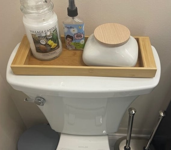 The tray on a reviewer's toilet with a candle, spray, and a jar on it