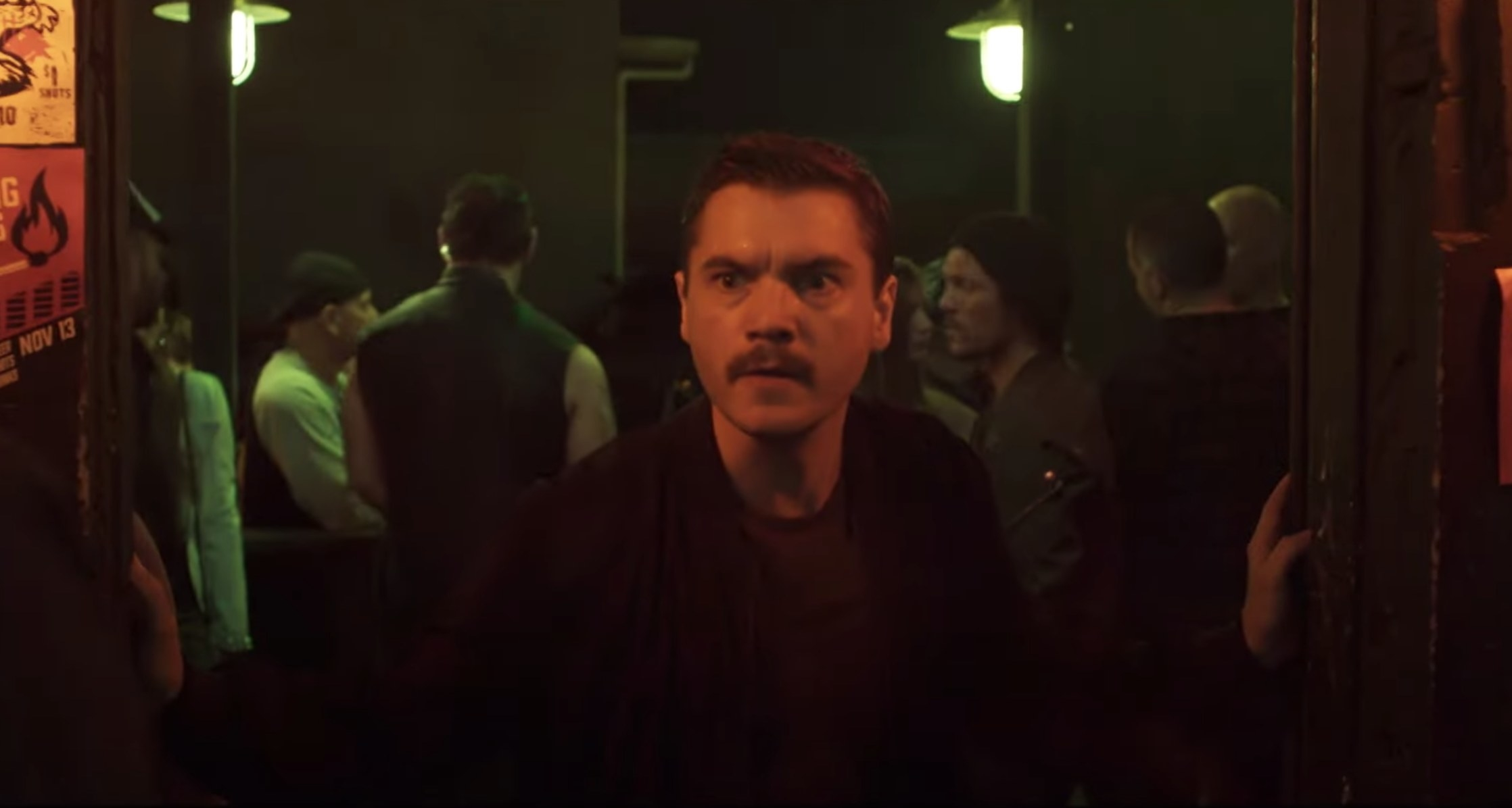 Emile walks into a bar and looks concerned in a screenshot from the film