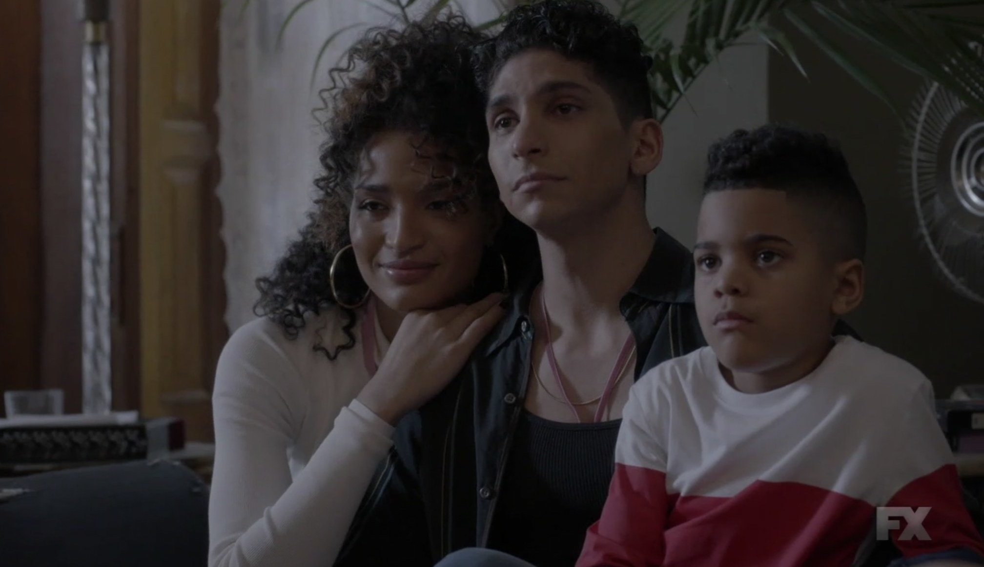 Angel, Papi, and son sitting very close and holding each other
