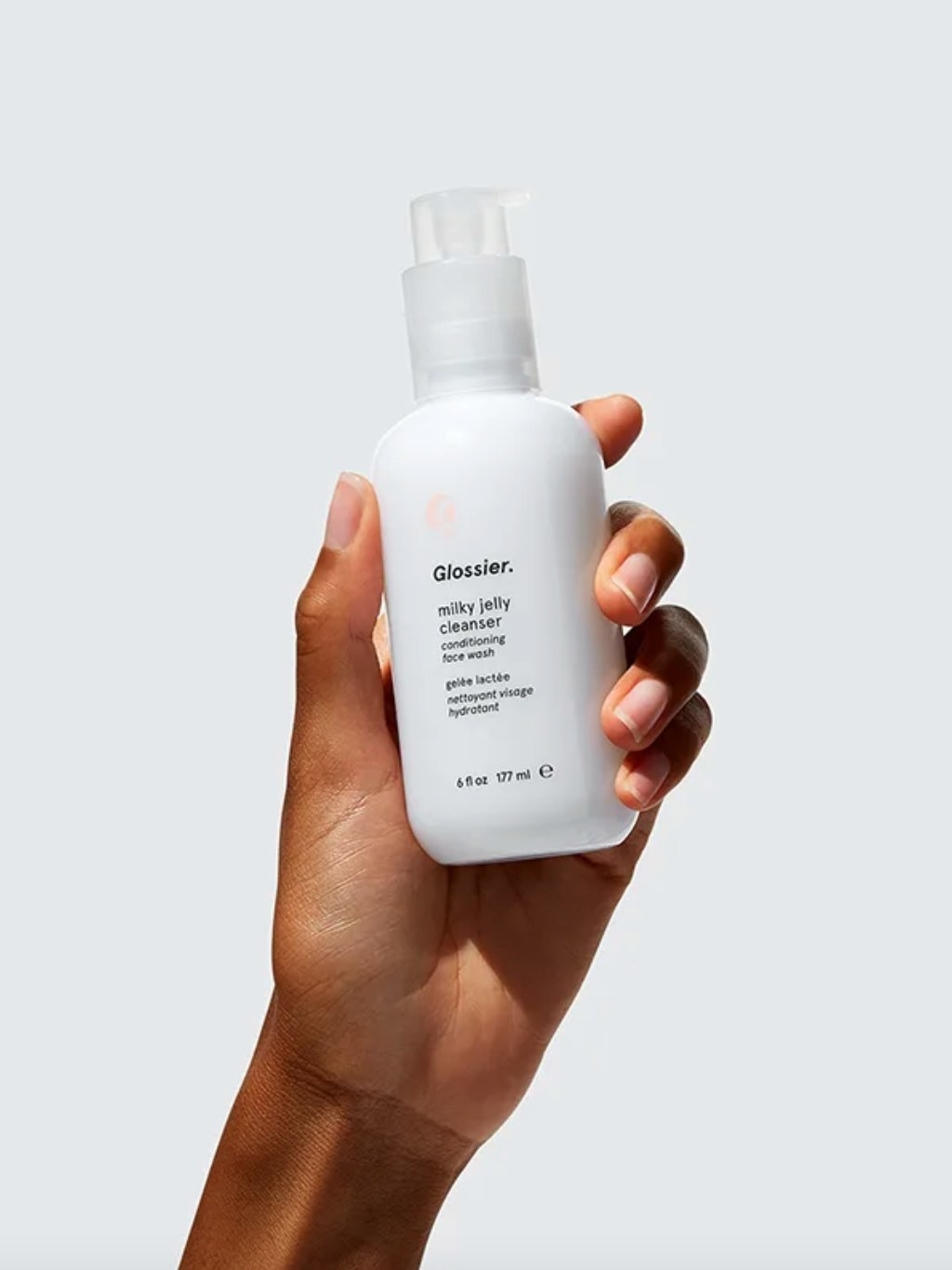 The Glossier milky jelly cleanser in a white bottle being held by a model