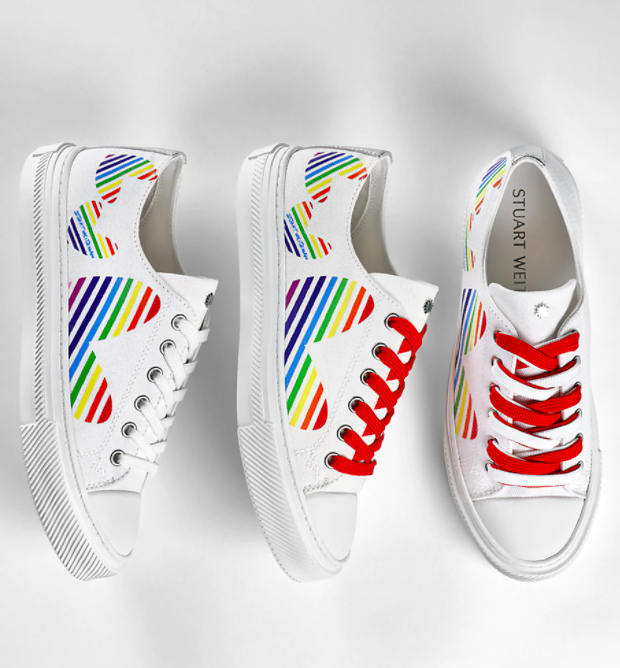 the sneakers which are white with big hearts on them with rainbow stripes, red and white shoelaces, and white shell-toes