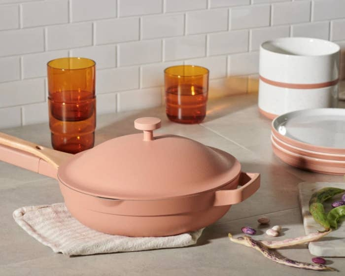 The always pan in blush next to dishware