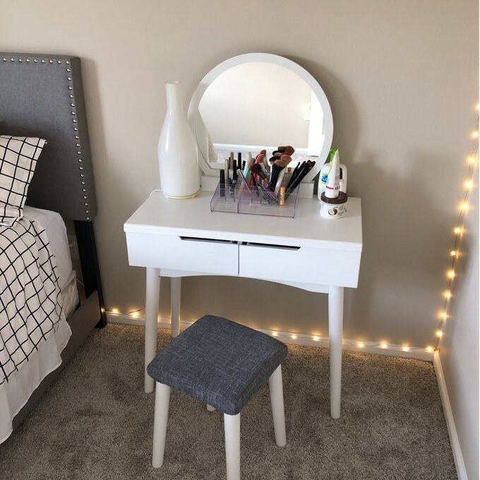 The white vanity with drawers and a round mirror attached, also a stool