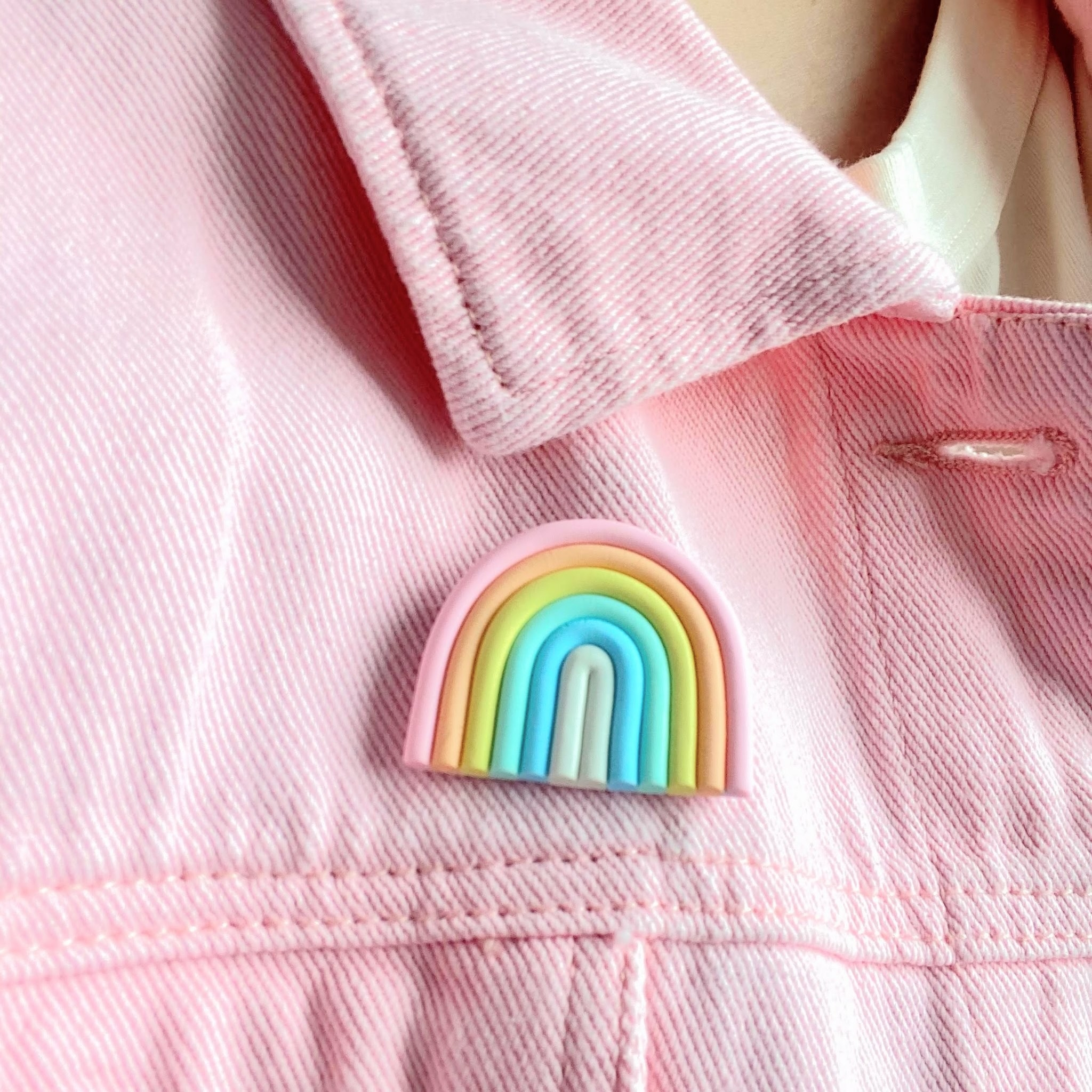 Rainbow-shaped clay pin on light pink denim jacket