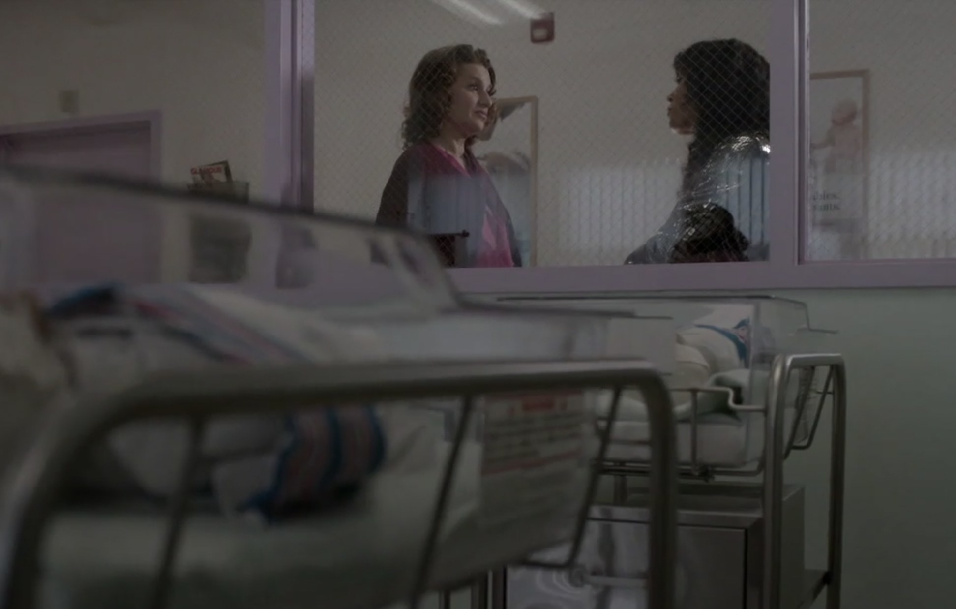 Nurse Judy standing with Blanca outside the window of the hospital's maternity ward, two swaddled babies in hospital cribs in the foreground