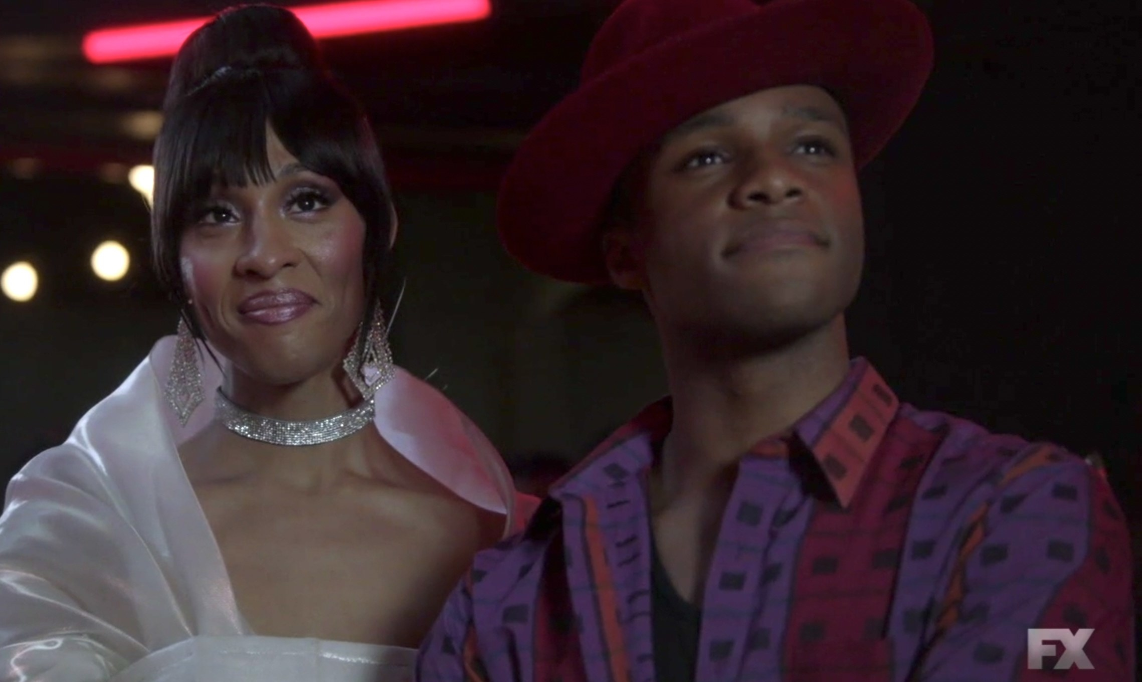 Blanca in a delicate shawl and sparkling collar necklace and earrings with an updo, next to Ricky in a wide brim hat and patterned button down shirt with lines and squares