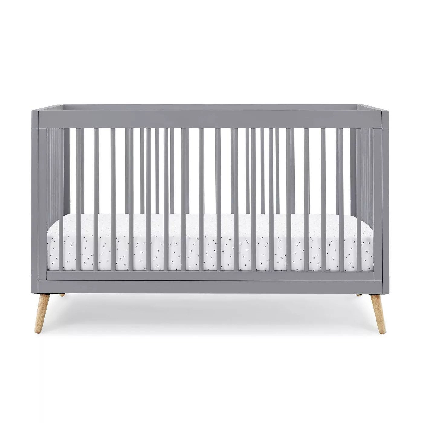 The gray crib with light wooden legs