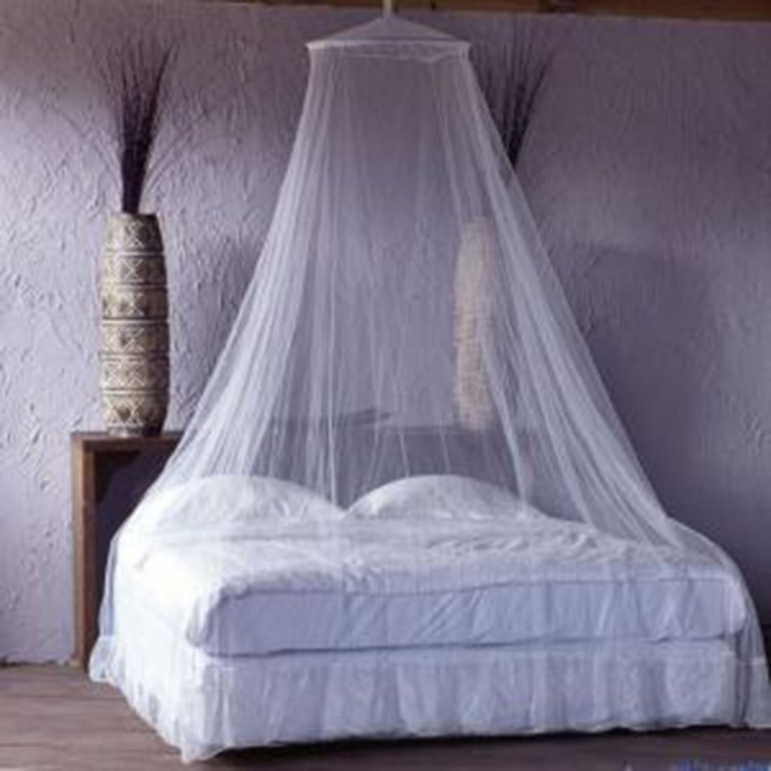 A canopy over a white bed beside some potted plants