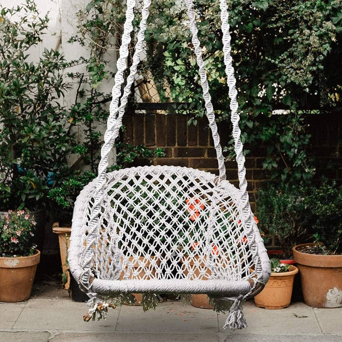 A jute swing chair in a balcony beside some potted plants