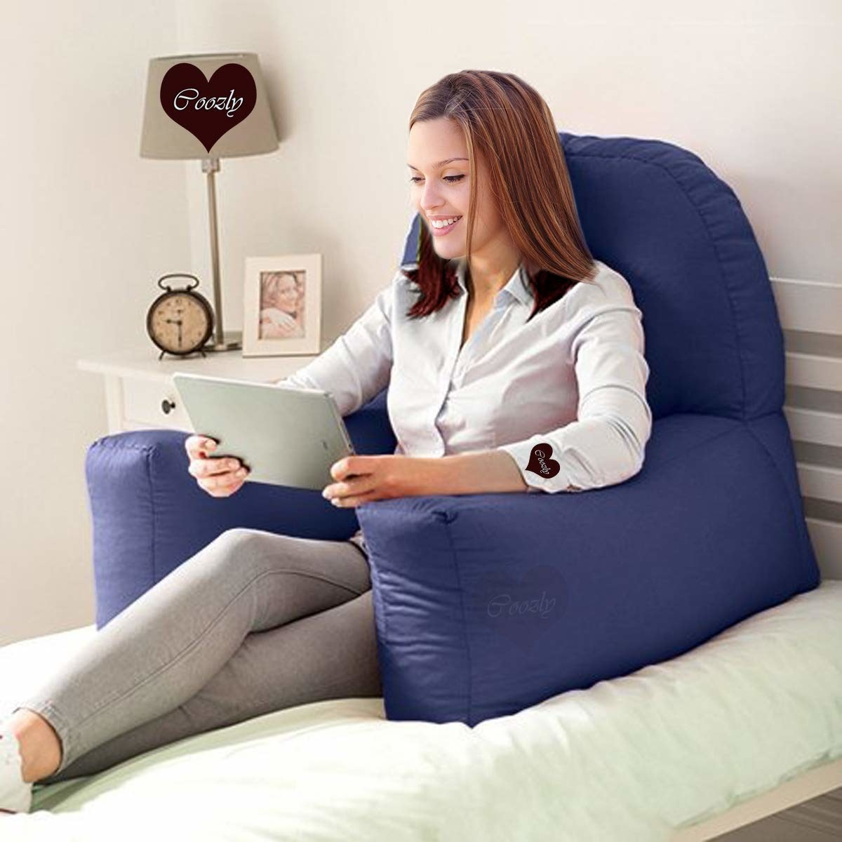 A person sitting on a bed with the bear hug pillow behind them, reading something on a tablet