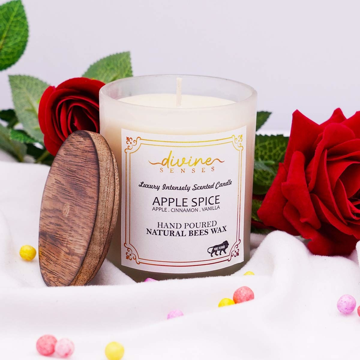 An apple spice scented candles next to roses and some beads