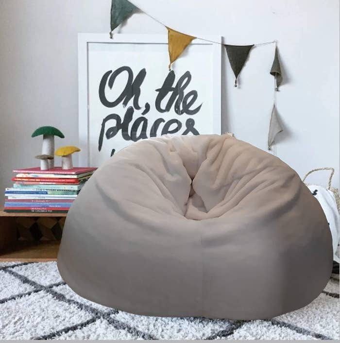 A bean bag on a shag carpet beside a poster and some books