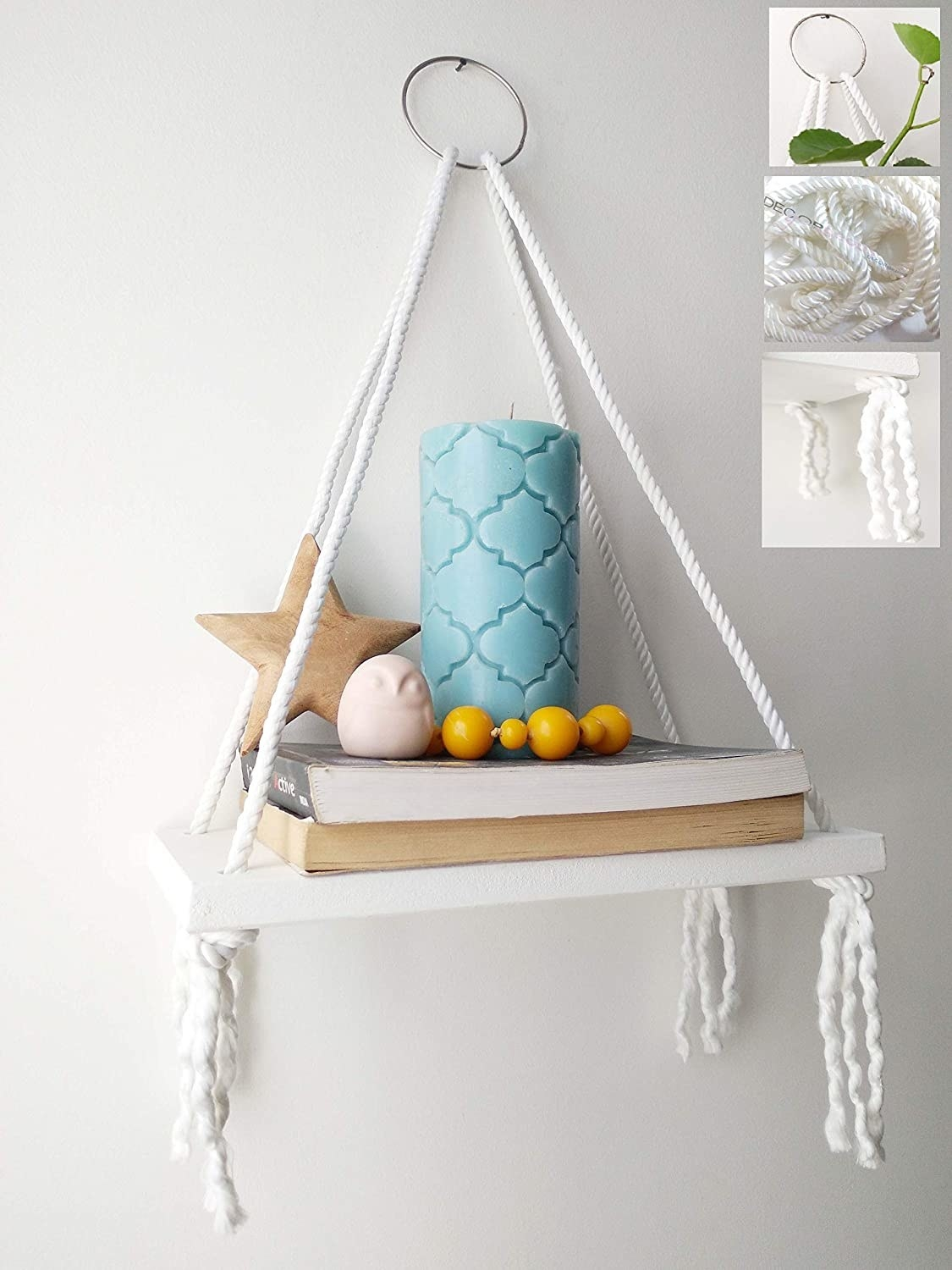 A hanging shelf with some books, a candle and some decoratives on it.