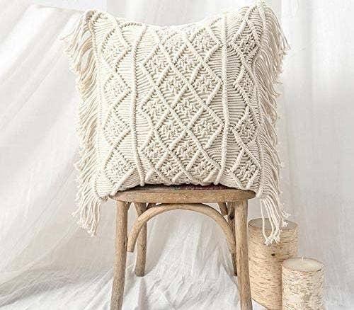 A macrame throw pillow on a stool