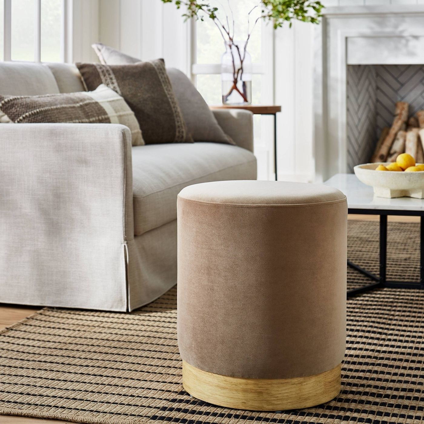 a tan velvet cylindrical ottoman with a wooden base