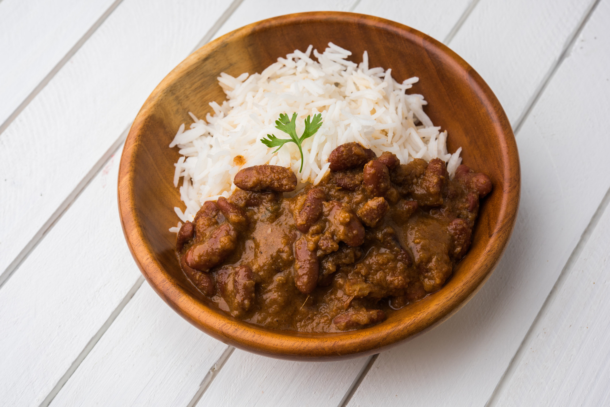 A bowl of rajma or kidney bean curry served with a side of basmati rice, garnished with a sprig of coriander