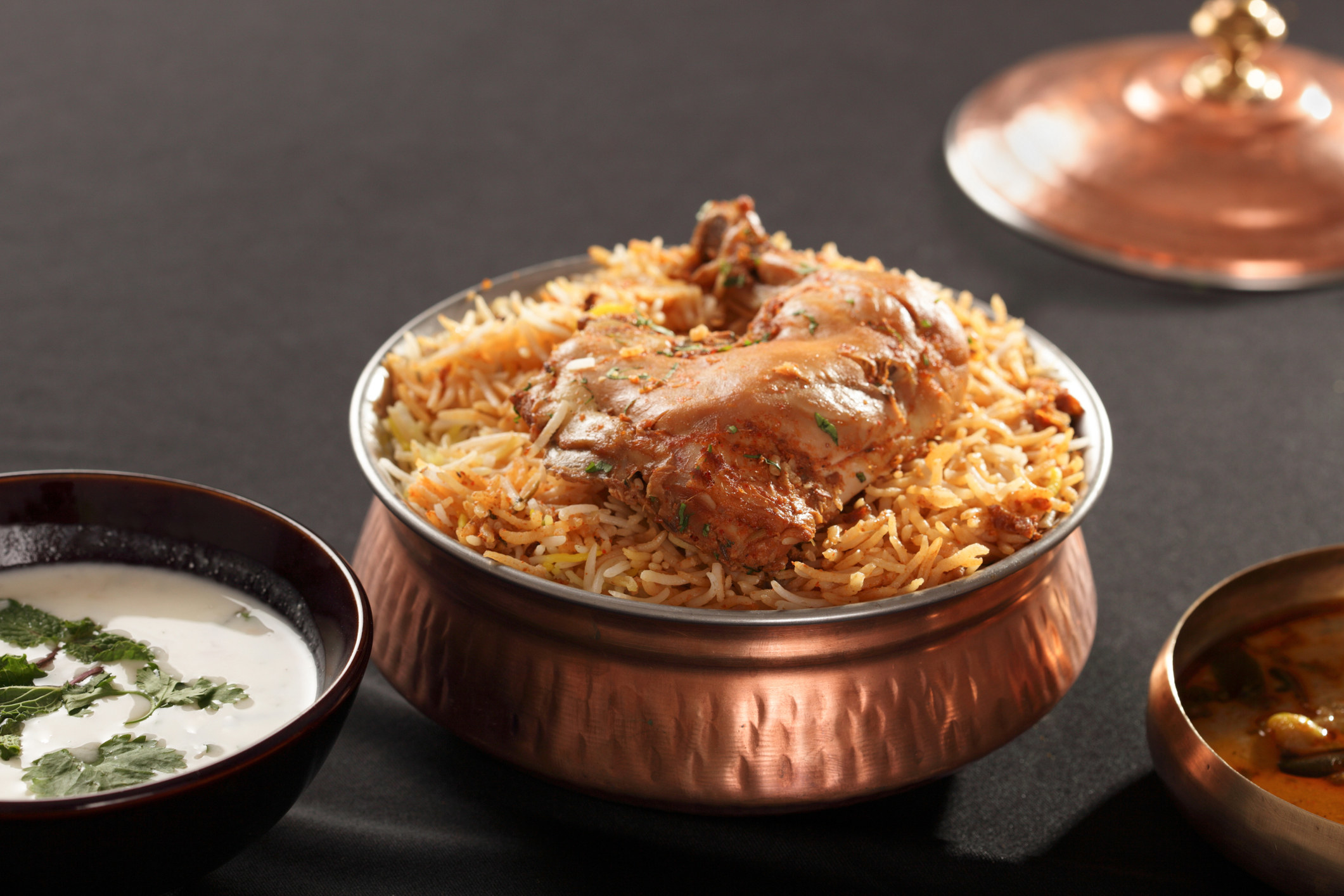 Chicken biryani, served in a copper bowl with a side of raita