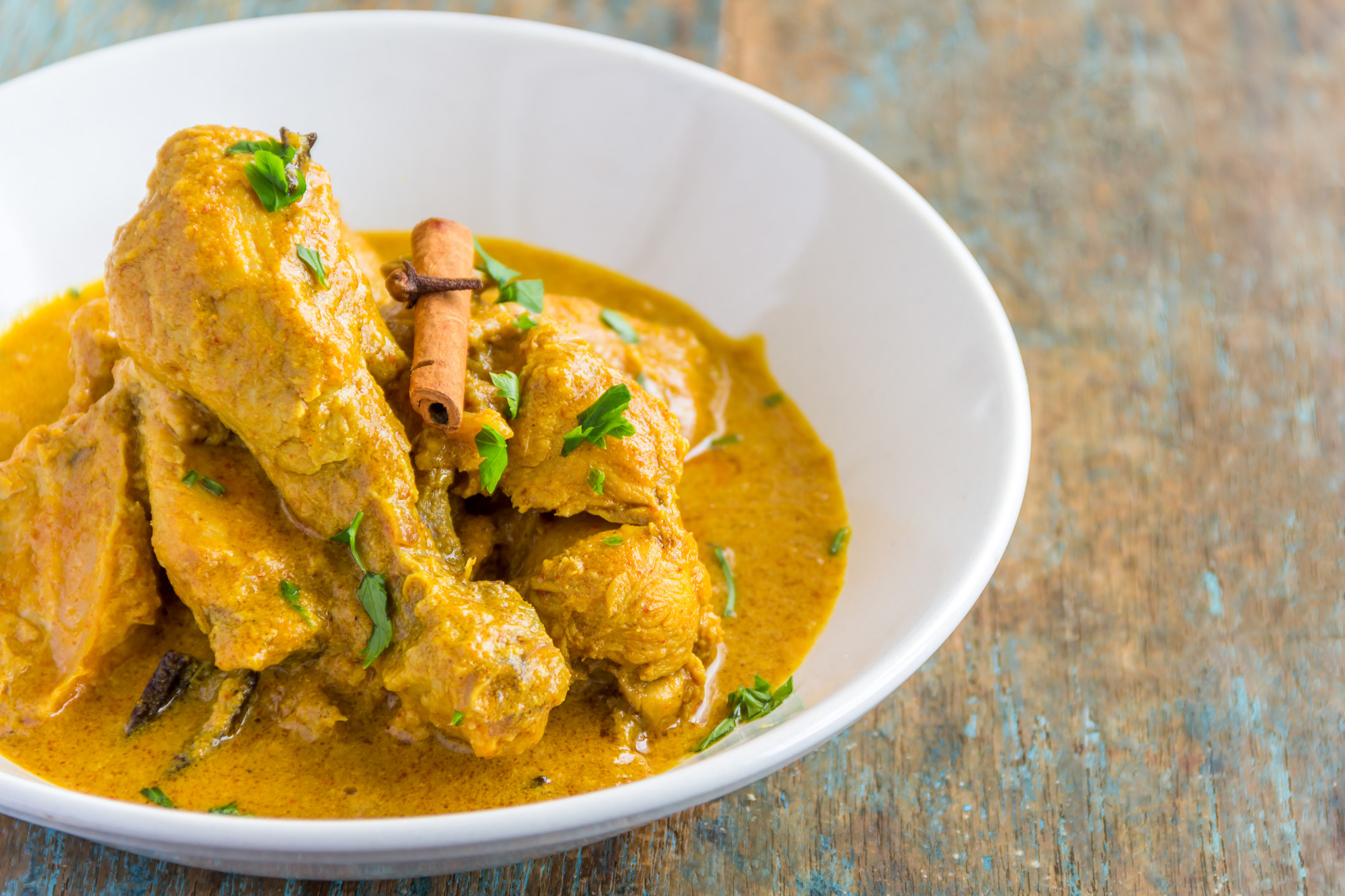 A bowl of chicken curry garnished with coriander and a stick of cinnamon