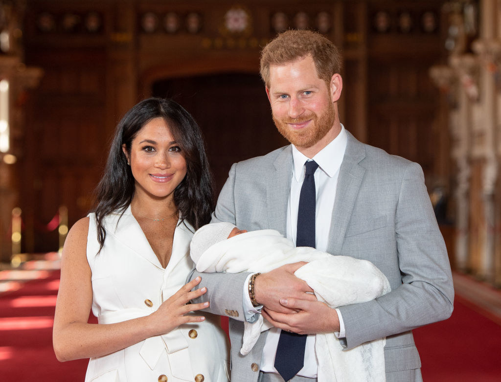 Prince Harry holds then-newborn son Archie Harrison while standing next to Meghan Markle