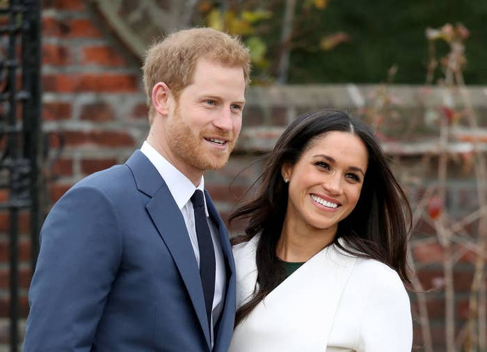 Prince Harry, wearing a blue suit, smiles for the camera while posing next to wife Meghan Markle, who is wearing a white coat