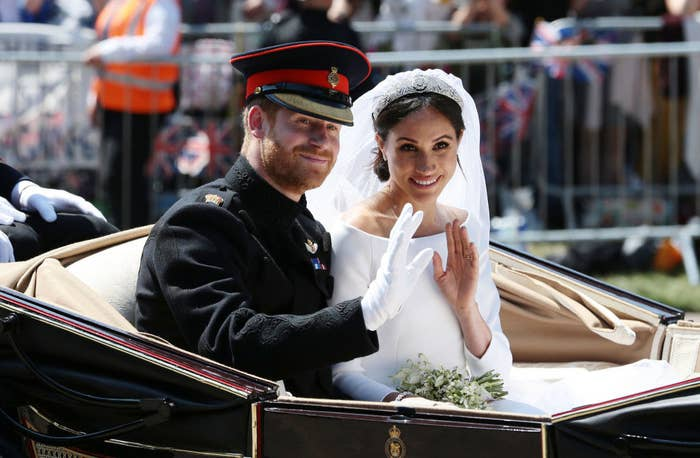 Prince Harry and Meghan Markle wave to crowds on their wedding day while riding in a carriage