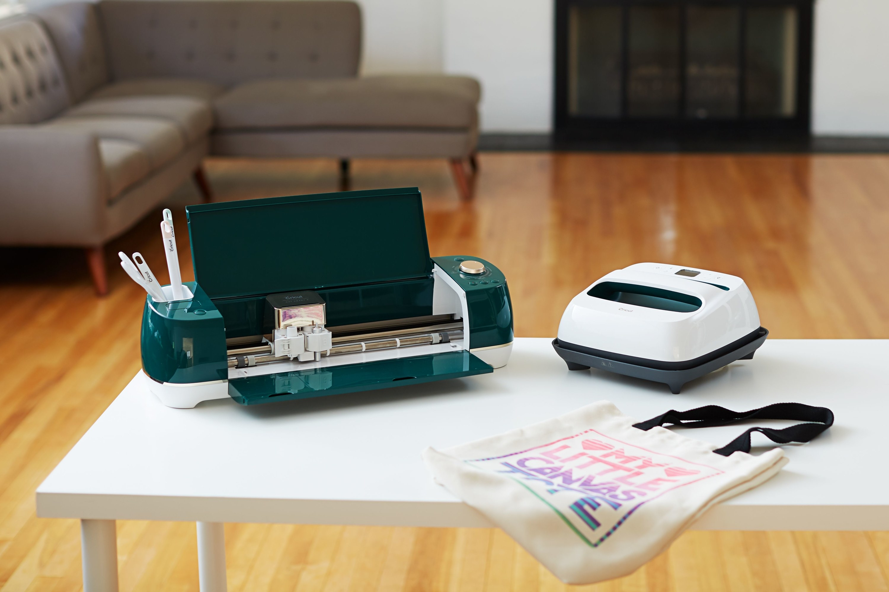 Cricut machine on a desk next to other crafting supplies