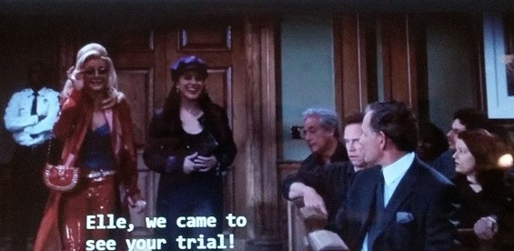 Margot wearing red pants, a red trench coat, a purple top, and red purse enters the courtroom. Serena who enters the courtroom with Margot is to her right and is wearing a black jacket and purple cap.