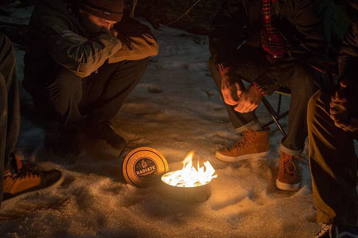 several campers sit around a radiate portable campfire on a beach