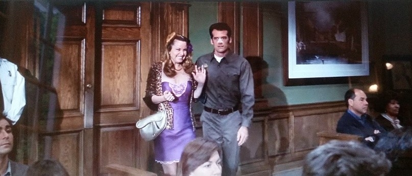 Paulette and the UPS guy have just entered the courtroom. Paulette wears a purple dress, leopard jacket, and flower in her hair. The UPS guy who is on Paulette's right has tape on his nose