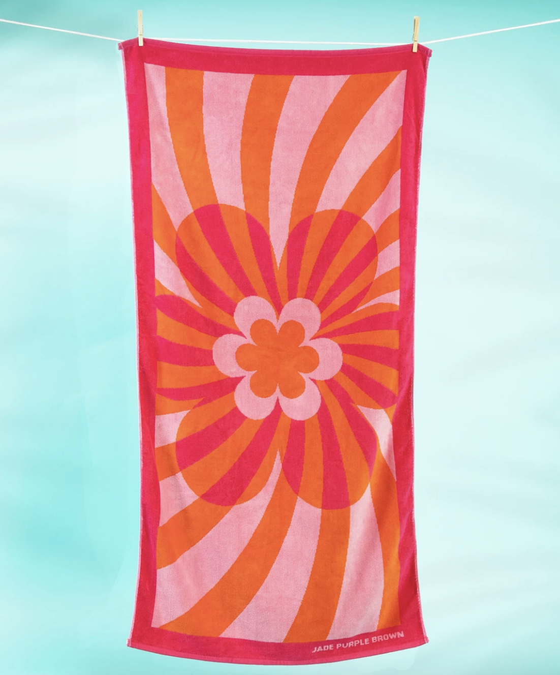 the flower power beach towel hanging from a clothesline
