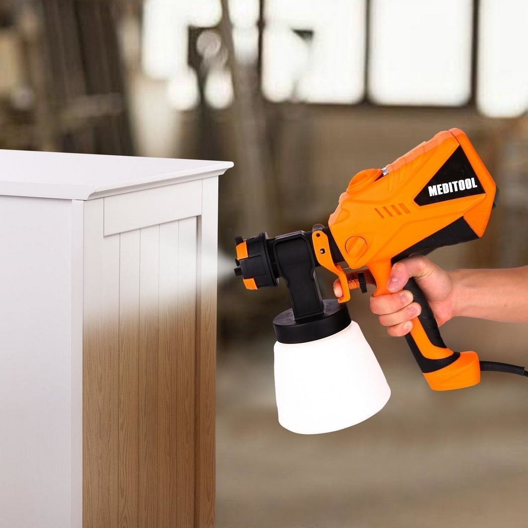 model using the electric paint sprayer to paint a cabinet white
