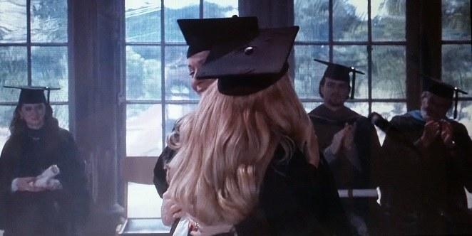 Elle wearing loose curls, a black cap, and gown, hugs Professor Stromwell.