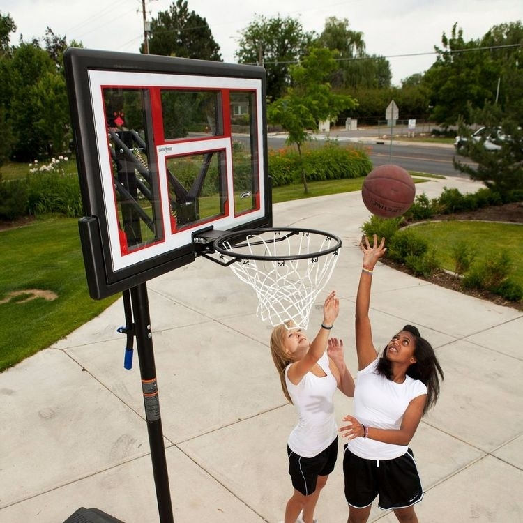 Two people jostle over a ball near the rim