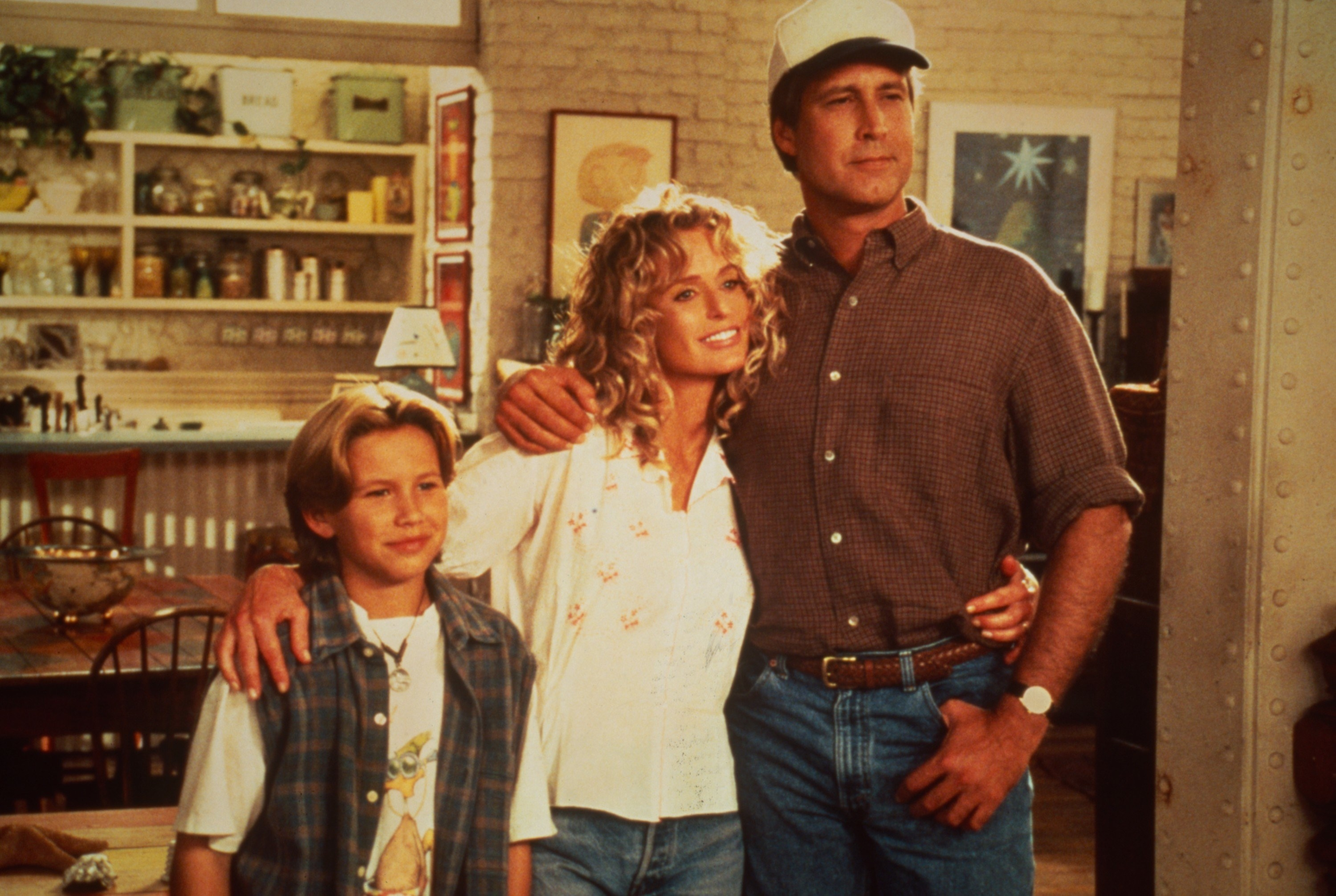 """Jonathan Taylor Thomas, Farrah Fawcett, and Chevy Chase pose on set of 1995's """"Man of the House"""""""