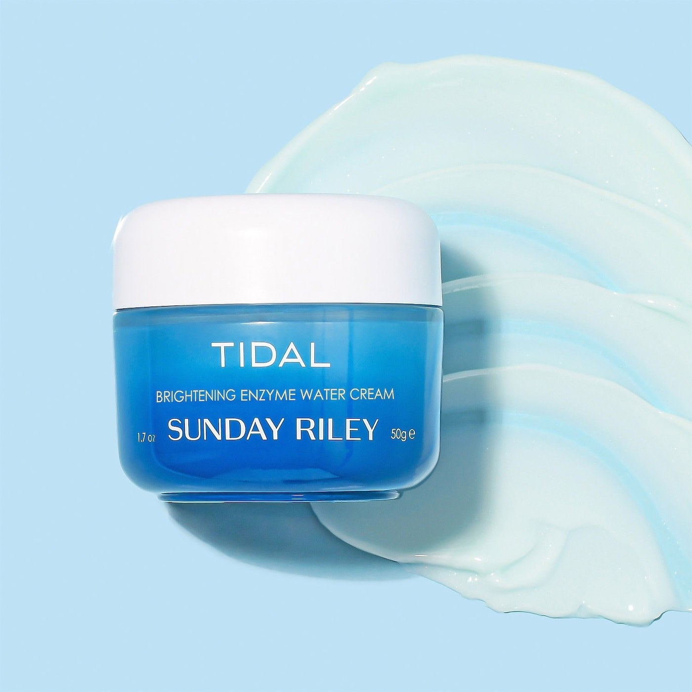 A blue bottle of skincare with a cream texture behind it