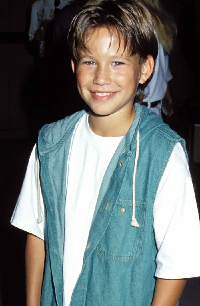 A youngJonathan Taylor Thomas smiles while wearing a denim vest, looking very '90s