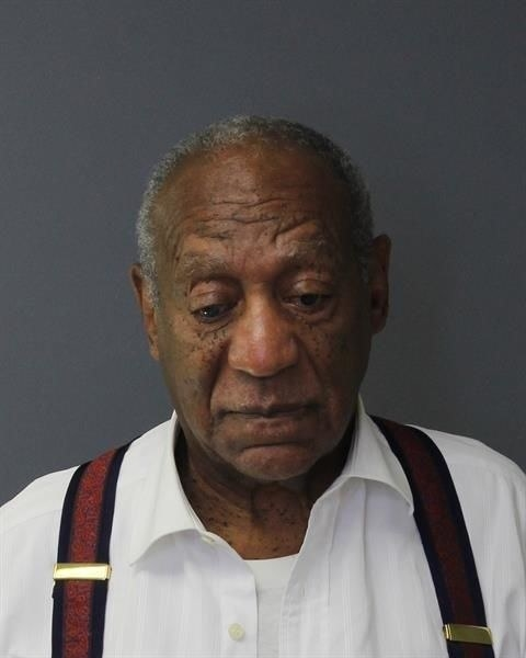 Bill Cosby wearing suspenders and looking down