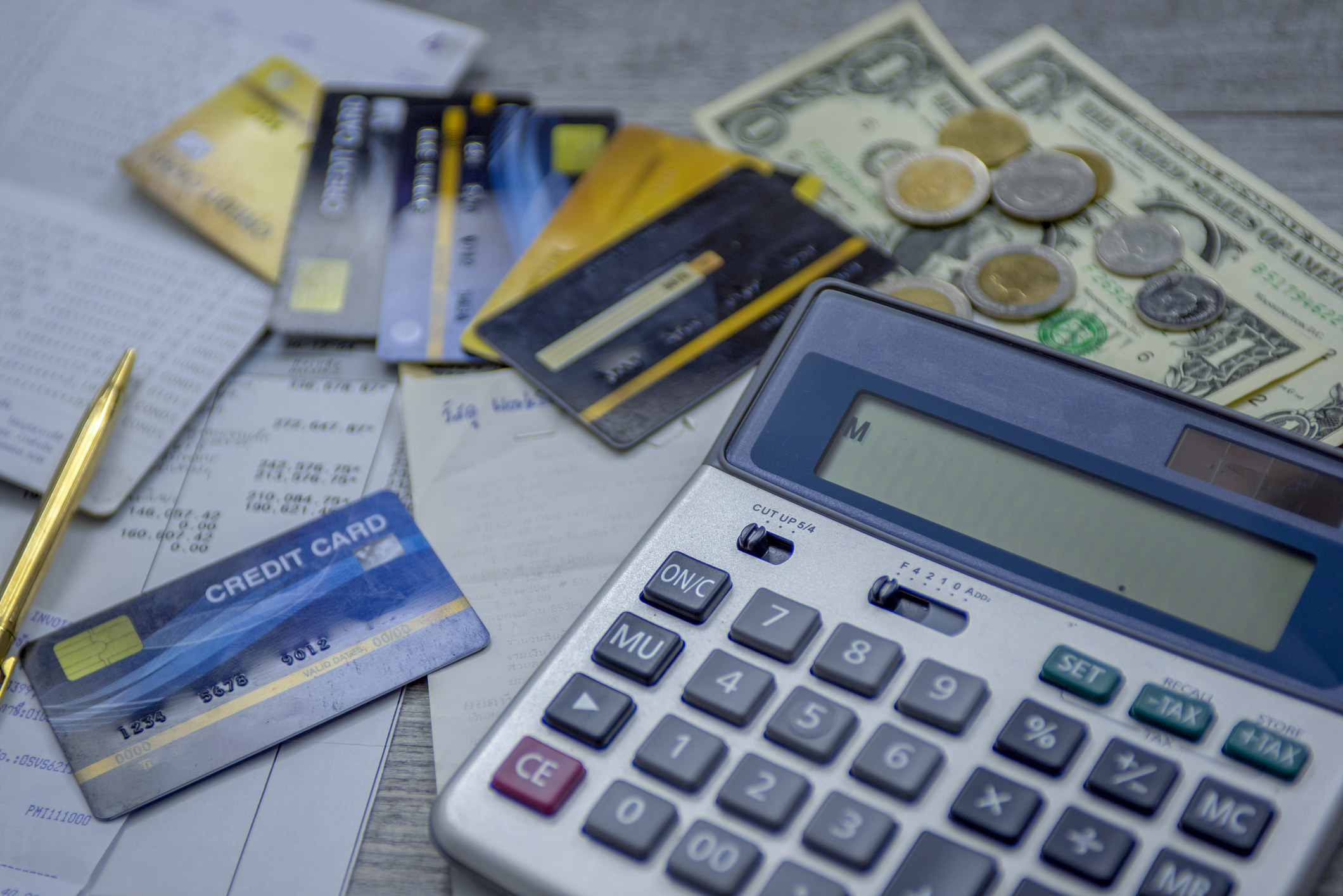 A calculator among credit cards, money, and lots of bills