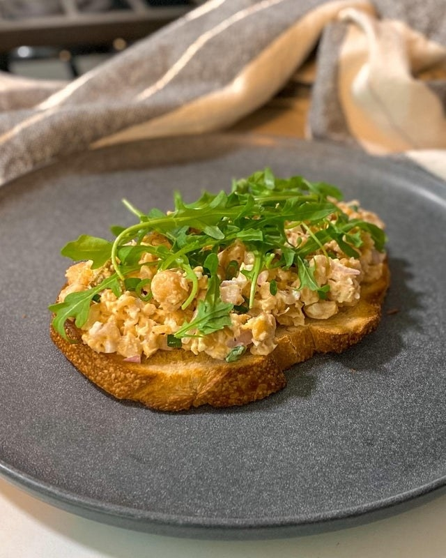 A piece of bread topped with chickpea salad.