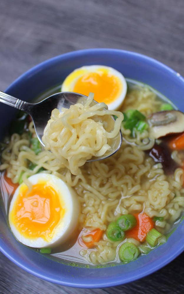 A bowl of instant ramen with a soft boiled egg and added vegetables.