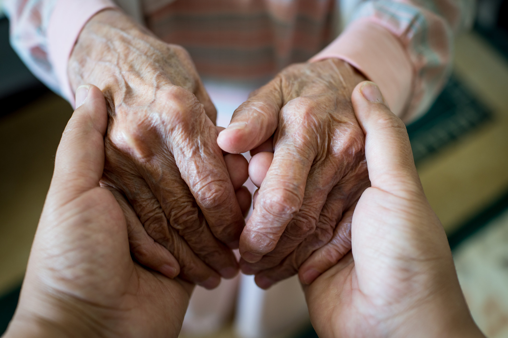 A young person holds the hands of an elderly person
